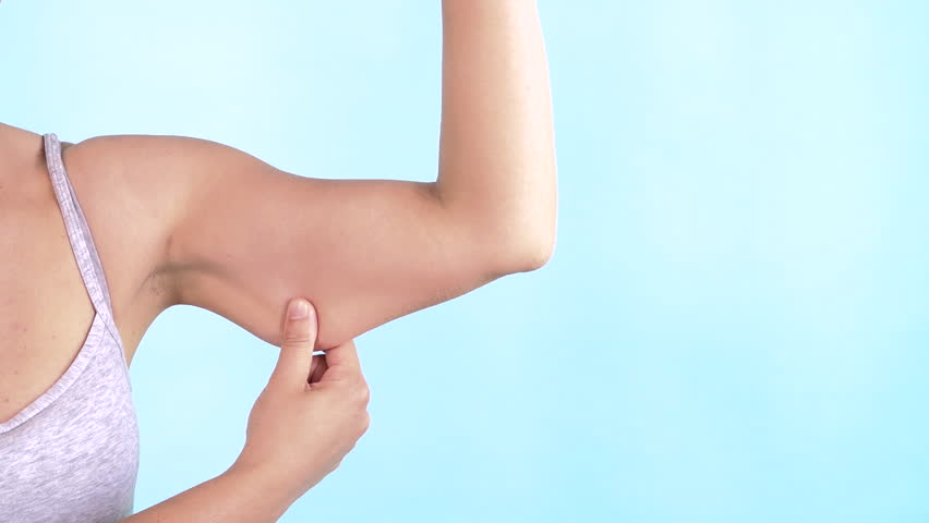 Chubby woman pinching upper arm fat isolated on blue background. Close up of caucasian female hand checking flabby skin. Body control, time to go on diet and weight loss concept