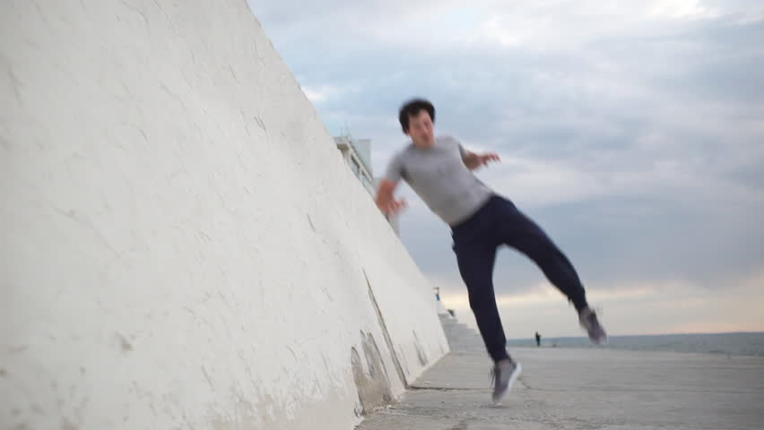Young Caucasian male gymnast jumping from wall and doing back somersault using thrusting off the wall in slowmotion