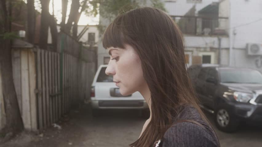 Pretty woman walking down an alleyway in an urban environment.   Shutterstock HD Video #27722137