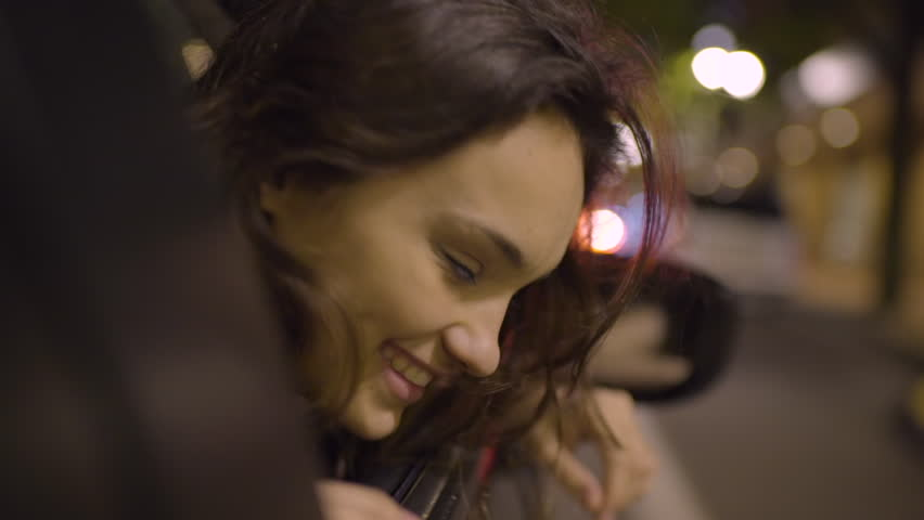 Carefree Woman Leans Out Passenger Side Car Window, Looks Around And Laughs (In City At Night/Slow Motion) #27728281
