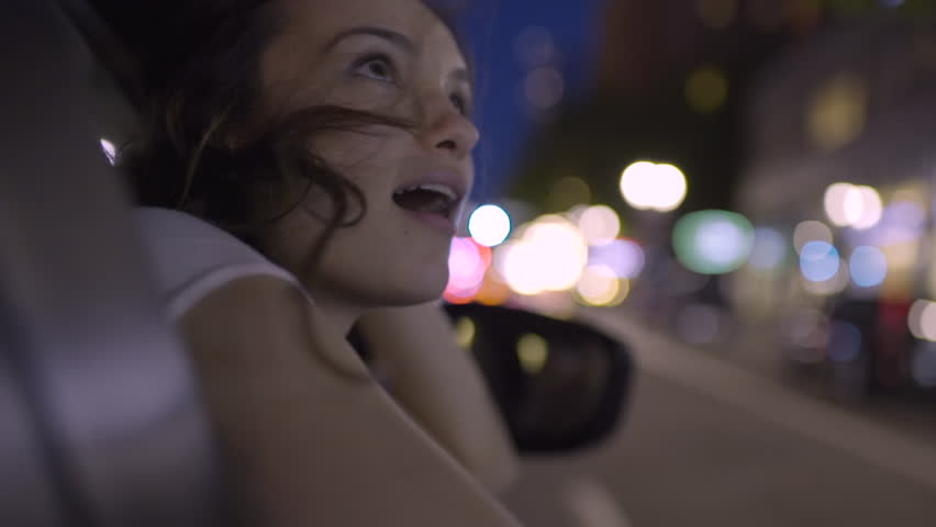 Happy Young Woman Leans Out Passenger Side Car Window, She Looks In Wonder And Awe At All The Beautiful Sights Of The City (Slow Motion) #27728296