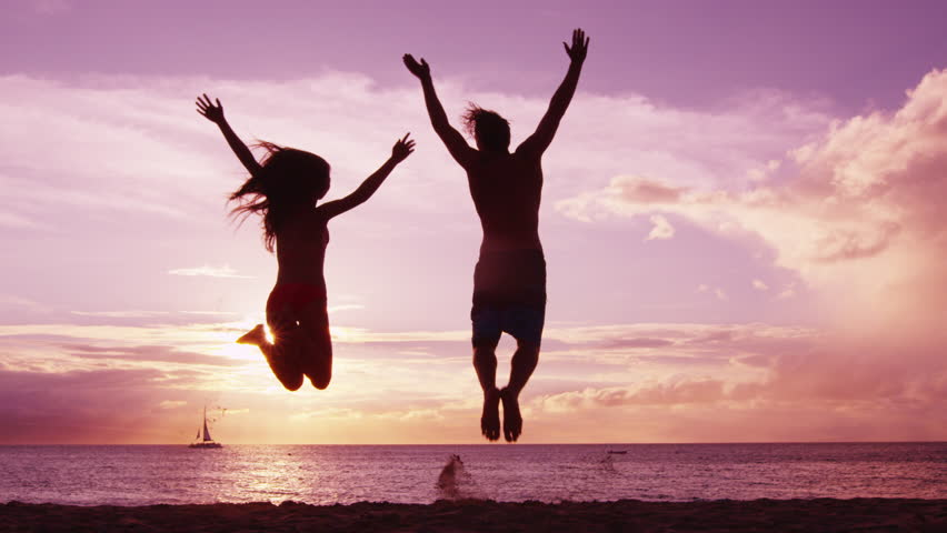 Happy couple jumping on beach enjoying sunset on summer travel vacation holiday. Happiness and bliss concept video with people jumping of joy celebrating in silhouette. SLOW MOTION RED EPIC.