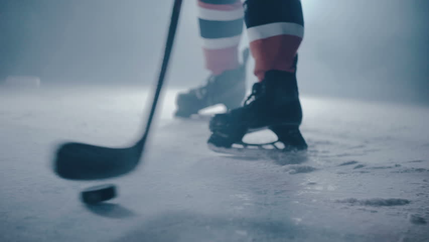 Hockey player hits the puck with a stick on ice close-up | Shutterstock HD Video #27736873