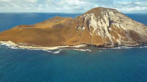 Aerial Flyover of Rabbit Island on Oahu Hawaii.  Near Makapuu beach, footage has deep blue ocean, blue skies and view down into crater.  Shot with 4K drone.
