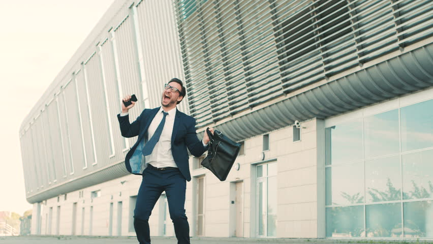 Happy stylish businessman hear good news on the phone and jumping with happy emotions outdoors near office building.