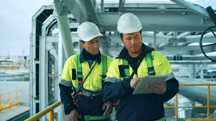 Two factory workers walking and discussion with tablet pc. Industrial background Royalty-Free Stock Footage #27800563