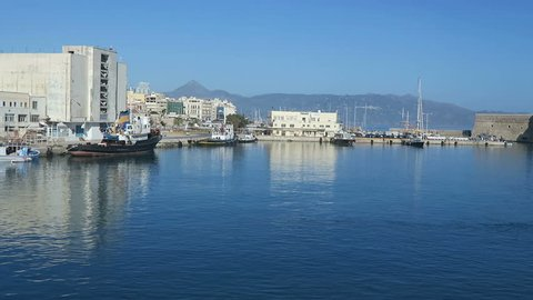 Iraklion, Crete / GREECE May 17 2017: Harbor of Iraklion on Crete (Greece). Ships and boats in the harbor right next to the historical town part of Iraklion with its fort.