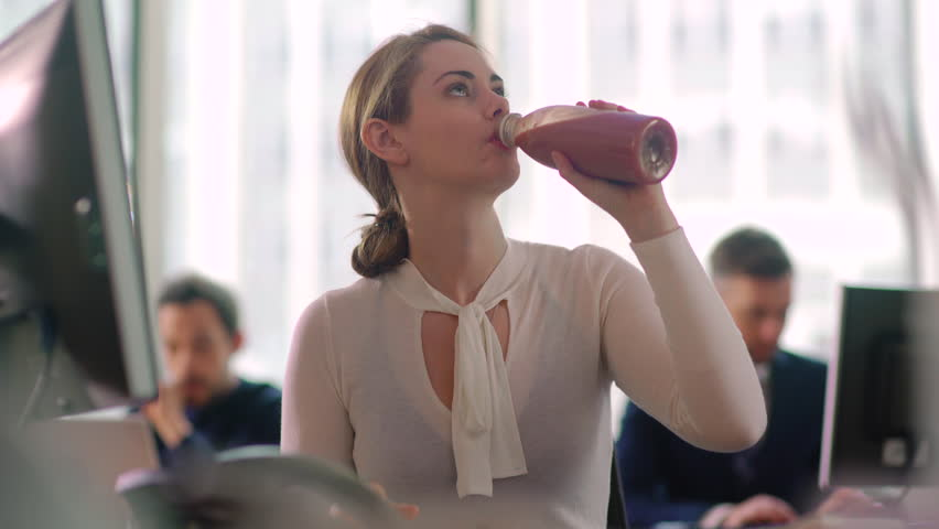 Woman sips a healthy smoothie drink whilst working at her desk.  Royalty-Free Stock Footage #27824161