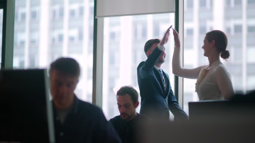 Business High Five - Office worker high five's a colleague as they walk passed people sitting at their desk. Royalty-Free Stock Footage #27824182