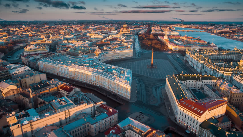 Aerial shot of the Palace Square and Alexander Column at sunset, a gold dome of St. Isaac's Cathedral, the Winter Palace, the Hermitage. St. Petersburg. Russia