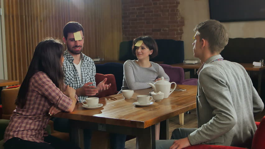 Young beautiful people at cafe table playing name game with sticker notes sticked to their forehead | Shutterstock HD Video #27839233