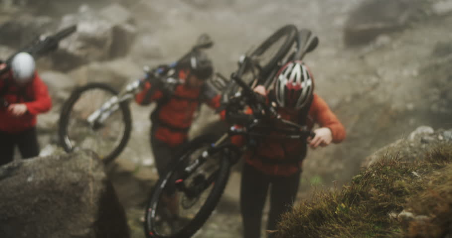 Medium shot of three mountain bikers straight on carrying their bikes up a hill during an extreme enduro race through fog up a mountain. Abstract slow motion shot of extreme sports preparation.