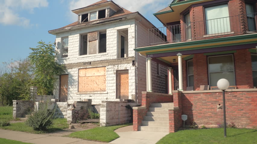 CLOSE UP: Driving past two residential buildings in contrast: beautiful inhabited semi-detached house with perfect mowed lawn vs. abandoned decaying home overgrown with wild plants, Detroit, America