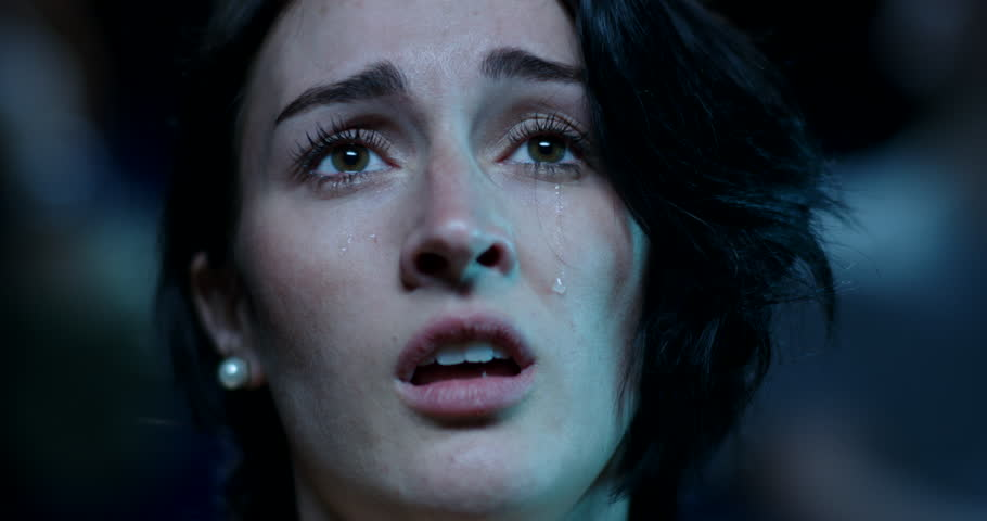 Tears stream down the face of a young woman while watching a sad and emotional movie