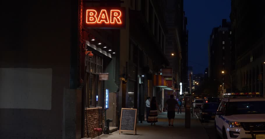 A nighttime exterior establishing shot of a generic, unbranded bar and restaurant in downtown Manhattan, New York. Day/Night matching available.