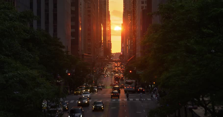 """A dramatic wide evening long establishing shot over 42nd Street in New York City during the """"Manhattanhenge"""" solar event."""