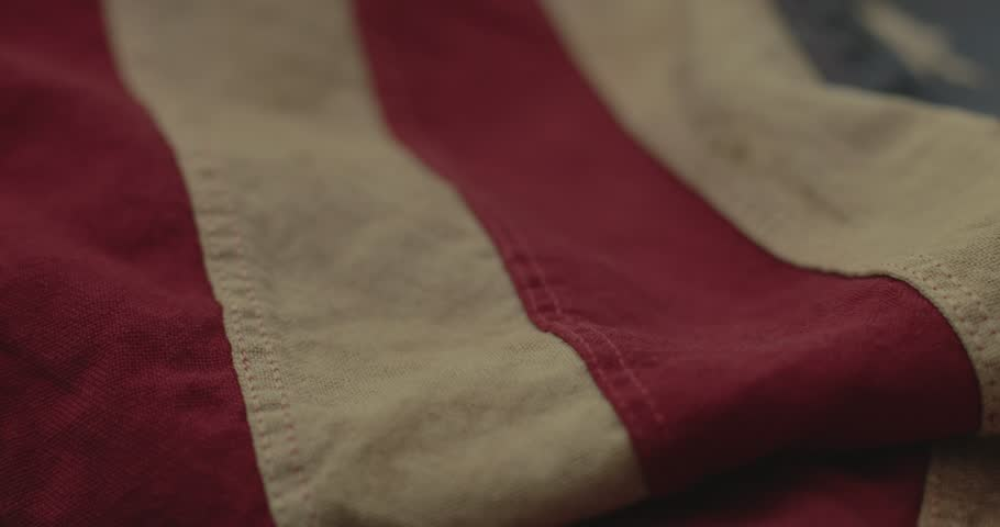 American flag detail with red and white stripes with field of blue and circle of 13 stars, the flag designed by Betsy Ross during the American Revolution. Shot in cinematic 4K.