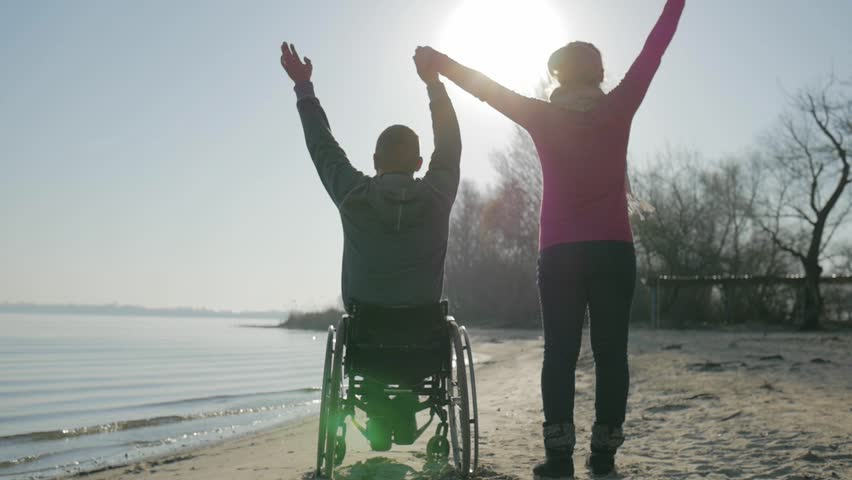 Disabled and girl raise their hands to top, handicapped person gives hand to girlfriend, back view