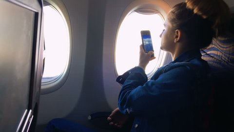 The girl climbs into the porthole and takes pictures of the landscape in the window on the phone. A young girl is traveling by plane. Slow motion 1080p