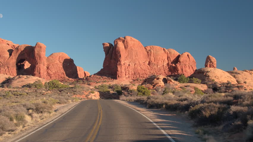 FIRST PERSON VIEW: Driving along an empty road through stunning Arches National Park in Utah on sunny day. Curvy road winding past the amazing red rock sandstone formations in hot desert United Stated