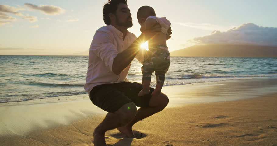 Young dad playing with baby son walking on the beach at sunset on vacation   Shutterstock HD Video #27893998