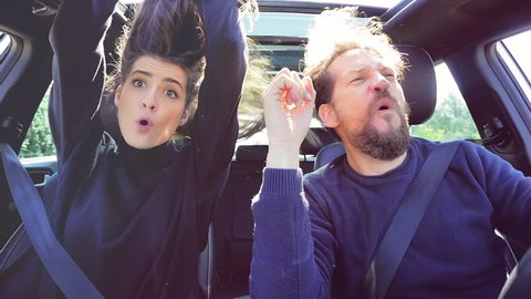 Happy people driving car dancing with wind blowing hair looking camera slow motion funny
