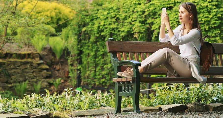 Woman Using Smartphone Relaxes in Sunny Park. SLOW MOTION 120 fps, 4K. Beautiful Millennial Woman on the Bench in Arboretum Taking Photos on cell phone camera. Social Media and blogging. | Shutterstock HD Video #27918778