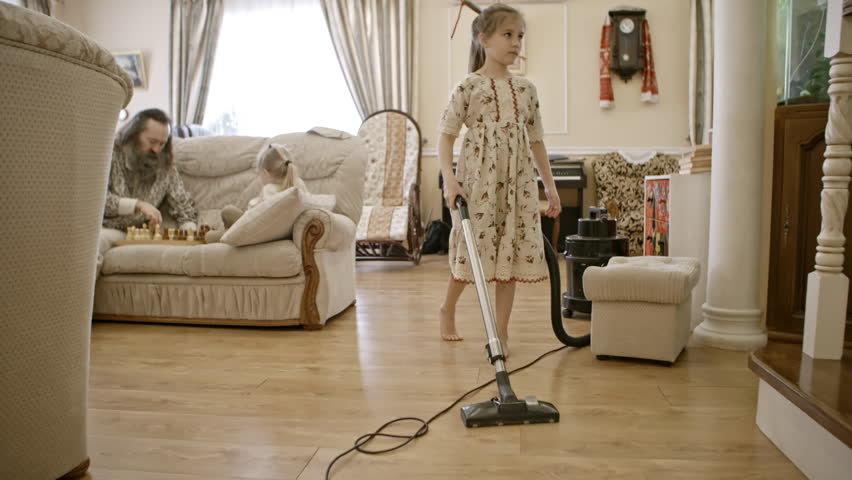 Barefoot little girl in traditional Russian dress cleaning floor in the living room with vacuum cleaner. Her dad and brother playing chess on sofa | Shutterstock HD Video #27923632