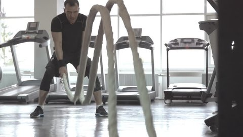 Slow motion of man with battle rope in functional training fitness gym