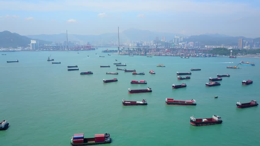 Fly over open water area with many small containers ship parked, aerial shot of Victoria Harbour west. Stonecutters island with many terminals seen ahead, cable-stayed bridge on left   Shutterstock HD Video #27949012