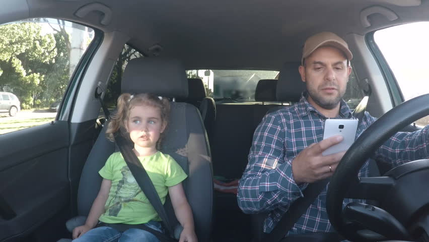 The father and his little daughter are driving in the car. A bad parent uses a smartphone while driving a car. Man texting and driving with his daughter in the car.