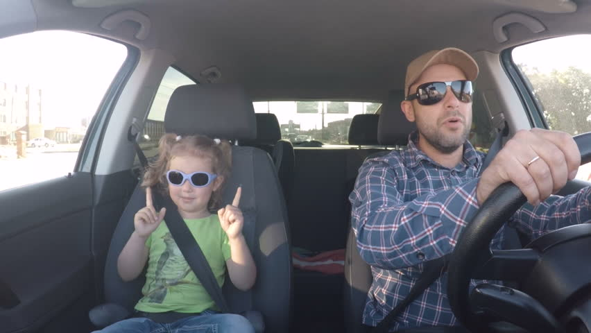 The father and his little daughter are driving in the car. Parent and child driving car having Sing a song  fun dancing