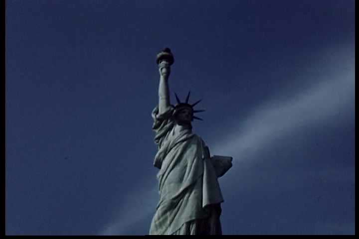 """1940s: Views of the Statue of Liberty precede moments during a Boy Scouts flag ceremony, in the final scenes from a film titled """"Flags on Duty"""". 