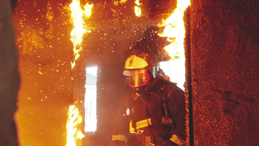 Three brave rescuers knock out the burning door and run into the smoke in the fire engulfed room. Raging fire