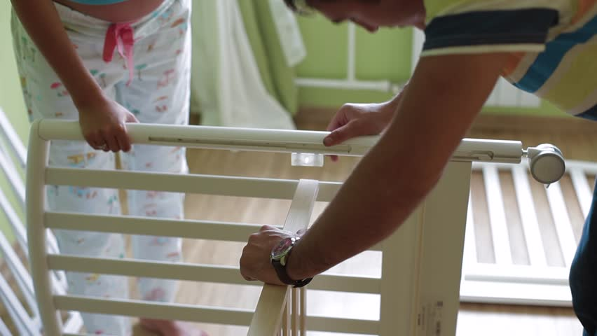 A woman and a man are collecting a baby cot. close-up.