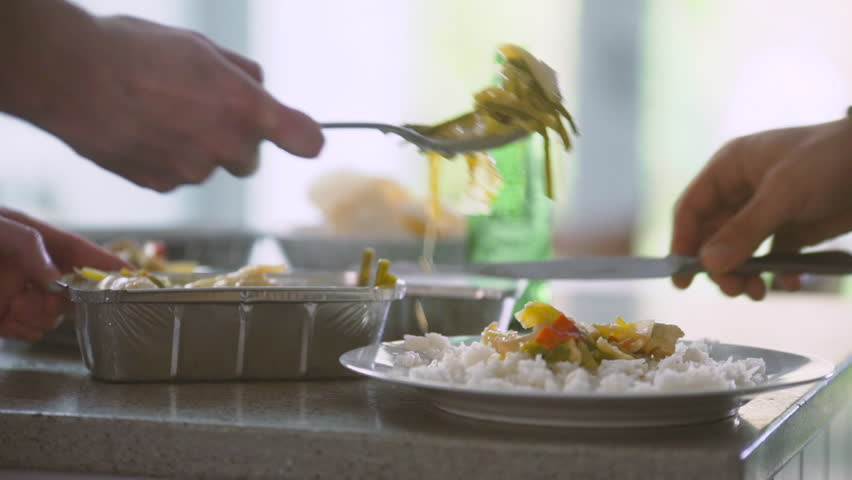 Plating up and serving a takeaway meal. 2 men prepare a takeaway meal together.  Royalty-Free Stock Footage #27981643