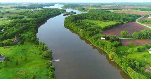 Calm river flowing through lush green Springtime landscape.