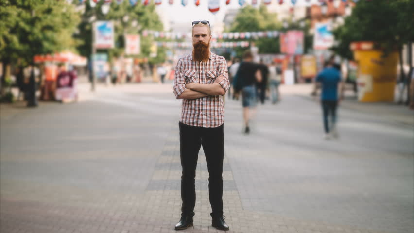 Zoom in timelapse of Young bearded man standing still at sidewalk in crowd traffic with people moving fast #27991039