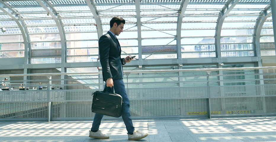A young handsome businessman (student) in a suit, comes with a briefcase, at the station, at the airport. Concept: a new business, traveling the world, communication, contacts, a new deal, success.
