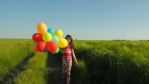 Child in nature with balloons. Little girl in the countryside with balloons.