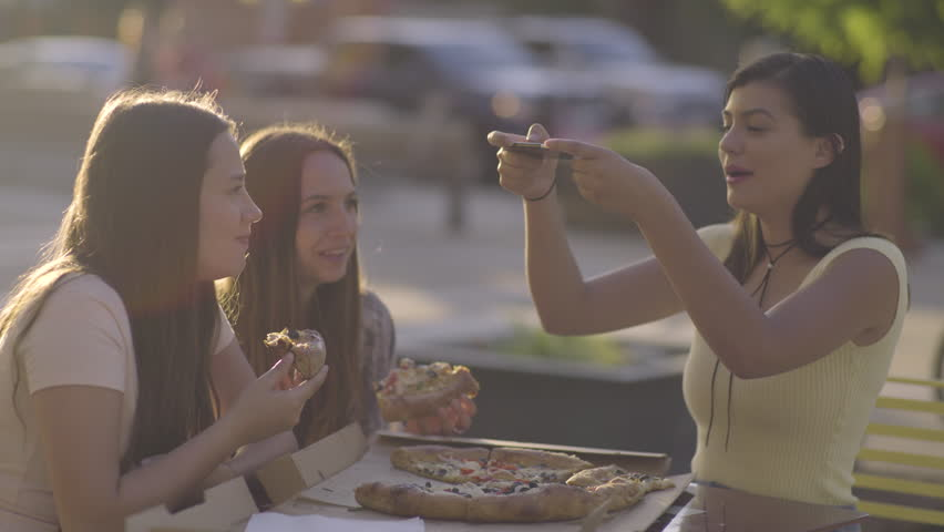 Carefree Hispanic Young Woman Tries To Take A Photo Of Pizza, Almost Drops The Phone On The Pizza, Funny/Everyone Laughs #28002706