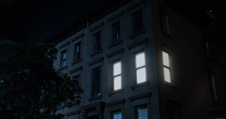 A nighttime exterior establishing shot of the upper floors of a typical Brooklyn brownstone residential home as a room lights up then turns off.     Shutterstock HD Video #28018423