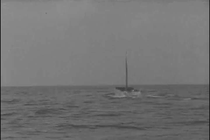 1940s: A U-boat breaks water and sails on the surface with the Nazi flag waving in the ocean in 1943.