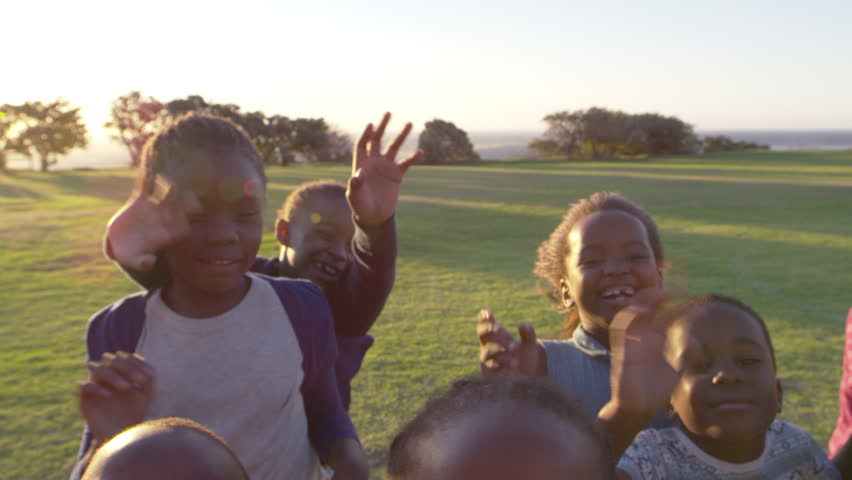 Elementary school kids waving to camera outdoors, close up #28048903