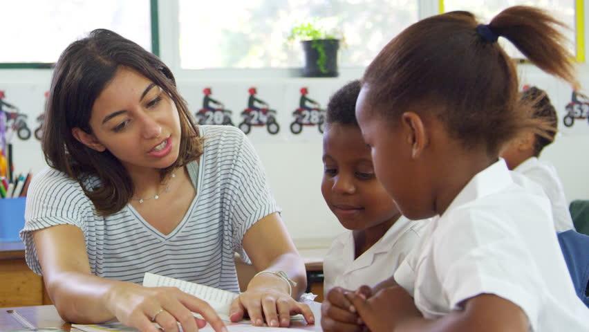 Volunteer teacher helps young school kids in class, close up