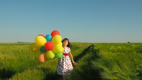 Happy child in a wheat field with balloons. The child is running with balloons.