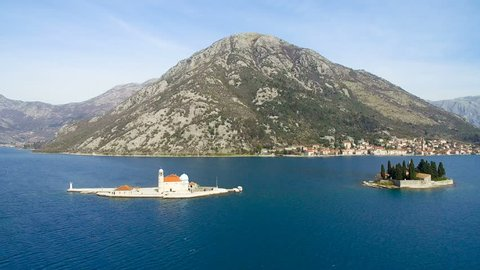 Island with  temple in  sea against backdrop of  mountain aerial view