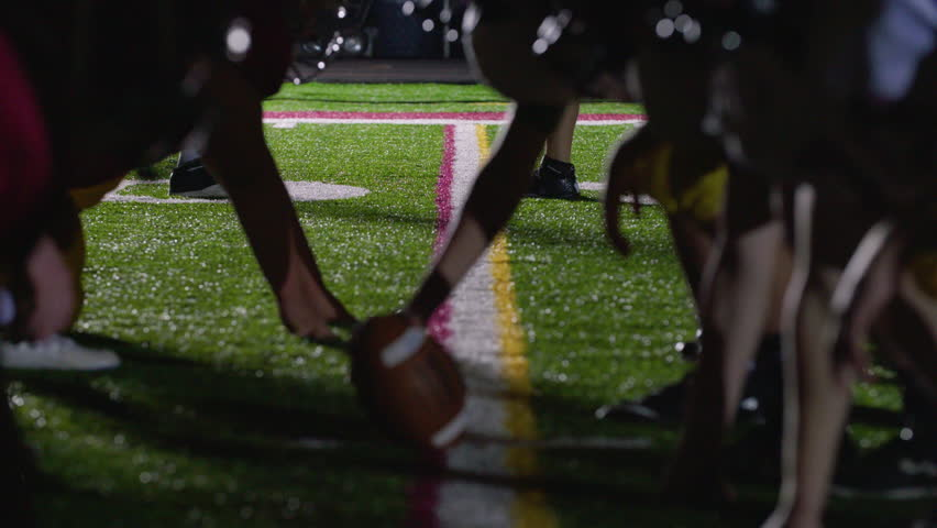 Close up of a football, as players get set at the line of scrimmage