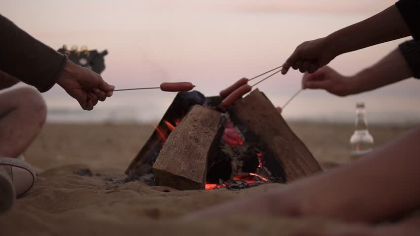 Group of young friends sitting by the fire on the beach, grilling sausages and playing guitar. Slowmotion shot #28078084
