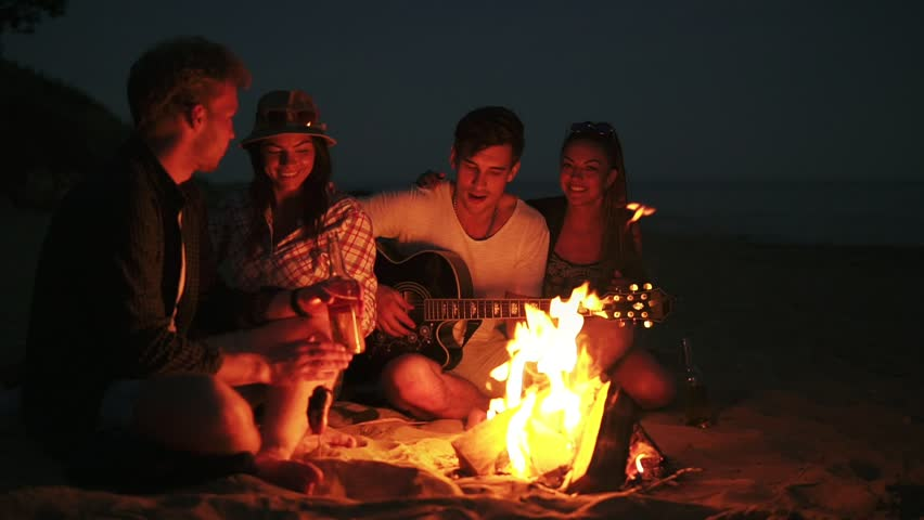 Picnic of young people with bonfire on the beach in the evening. Cheerful friends singing songs and playing guitar. Slowmotion shot